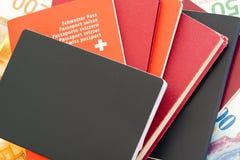 Pila de los pasaportes de cierre para arriba con un pasaporte suizo detalladamente y el dinero del franco suizo en el fondo fotos de archivo
