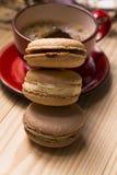Pila de macarons y taza de café roja en un backgr de madera ligero foto de archivo libre de regalías