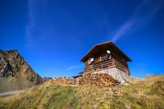 Pila de madera delante de la cabina y de las montañas de Fagaras imágenes de archivo libres de regalías