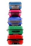 Pila de maletas plásticas en blanco Foto de archivo libre de regalías