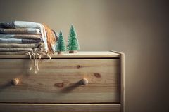 Pila de mantas a cuadros beige de las lanas y de dos árboles de navidad en del pecho de madera todavía del invierno una vida acog imagen de archivo libre de regalías