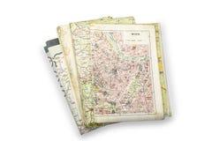 Pila de mapas usados con Viena una en el top en el blanco fotos de archivo