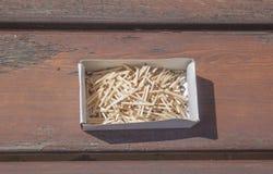 Pila de matchsticks en la caja en un banco de madera Fotos de archivo