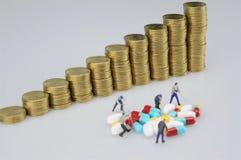 Pila de moneda de oro y de gente miniatura con la medicina imagen de archivo