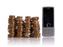 Pila de monedas BRITÁNICAS contra el teléfono móvil fotos de archivo libres de regalías
