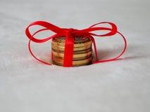 Pila de monedas como regalo de la Navidad que miente en la nieve fotos de archivo libres de regalías