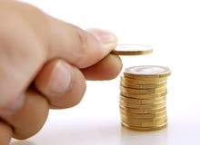 Pila de monedas con una mano que añade una más moneda Foto de archivo libre de regalías