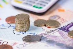 Pila de monedas de libra británica sobre gráfico Imagen de archivo