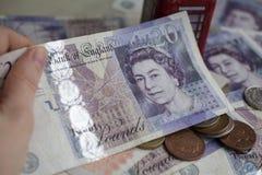 Pila de monedas de libra en veinte notas de la libra Imagenes de archivo