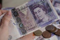 Pila de monedas de libra en veinte notas de la libra Imagen de archivo