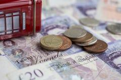 Pila de monedas de libra en veinte notas de la libra Imágenes de archivo libres de regalías