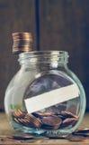 Pila de monedas de un centavo en el final de cristal del tarro Fotografía de archivo libre de regalías
