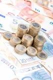 Pila de monedas en billetes de banco Imagen de archivo libre de regalías