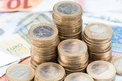 Pila de monedas en billetes de banco Fotos de archivo libres de regalías