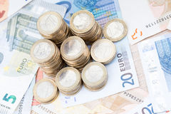 Pila de monedas en billetes de banco Fotos de archivo