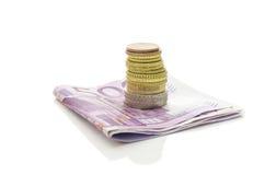 Pila de monedas euro en billetes de banco Imagenes de archivo