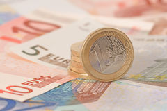 Pila de monedas euro en billetes de banco euro Imagen de archivo libre de regalías