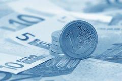 Pila de monedas euro en los billetes de banco euro (azul entonado) Foto de archivo libre de regalías
