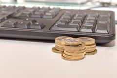 Pila de monedas de libra con un teclado fotos de archivo
