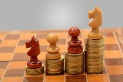 Pila de monedas de oro con el ajedrez - concepto del éxito Imagen de archivo libre de regalías