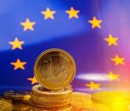 Pila de monedas un euro contra la perspectiva de la bandera del Fotografía de archivo