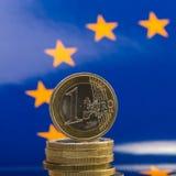 Pila de monedas un euro contra la perspectiva de la bandera del Imágenes de archivo libres de regalías
