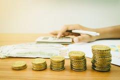 Pila de monedas y de billete de banco de oro del dólar Foto de archivo
