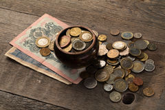 Pila de monedas y de billetes de banco en una tabla de madera Foto de archivo libre de regalías