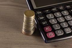 Pila de monedas y de calculadora Fotografía de archivo libre de regalías