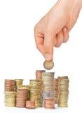 Pila de monedas y de mano euro con el euro 2 Foto de archivo libre de regalías