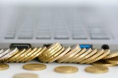 Pila de monedas y de un teclado del ordenador portátil Foto de archivo libre de regalías