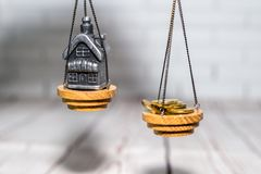 Pila de monedas y una pequeña casa en las escalas El concepto de opción, ahorros del efectivo y compra de las propiedades inmobil imágenes de archivo libres de regalías