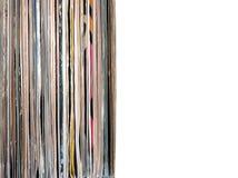 Pila de muchos discos de vinilo en viejas cubiertas del color en lado izquierdo en la foto en el fondo blanco foto de archivo libre de regalías