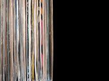 Pila de muchos discos de vinilo en viejas cubiertas del color en lado izquierdo en la foto en fondo negro fotografía de archivo libre de regalías