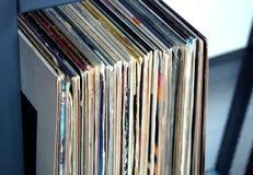 Pila de muchos discos de vinilo en viejas cubiertas del color en una vista lateral del estante foto de archivo