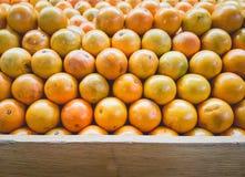 Pila de naranjas en soporte del estante de la fruta con la madera para el espacio a de la copia Foto de archivo libre de regalías