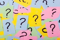 Pila de notas de papel coloridas con los signos de interrogación primer imagenes de archivo