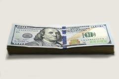 Pila de nuevos billetes de banco del ciento-dólar en el backgrond blanco Foto de archivo libre de regalías