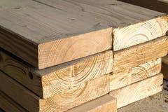 Pila de nuevos postes de madera en la yarda de madera de construcción Constr de madera de la madera imagen de archivo