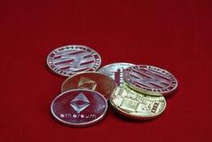 Pila de oro y de monedas de plata del cryptocurrency en un fondo rojo del terciopelo imagen de archivo libre de regalías