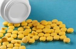 Pila de píldoras y de banco médicos en un fondo azul Foto de archivo