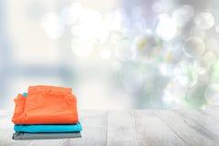 Pila de pantalones cortos coloridos para los niños en la tabla de madera brillante delante del fondo soleado brillante del bokeh  imágenes de archivo libres de regalías