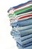 Pila de pantalones vaqueros y de camisetas coloridas Imagen de archivo