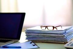 Pila de papeles en el escritorio con el ordenador imágenes de archivo libres de regalías