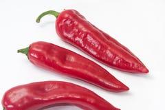 Pila de paprikas rojas en el fondo blanco Foto de archivo