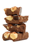Pila de pedazos del chocolate con las avellanas Imágenes de archivo libres de regalías