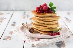 Pila de pequeñas crepes hechas en casa con la miel, las frambuesas frescas y las pasas rojas en un viejo fondo de madera ligero fotografía de archivo libre de regalías