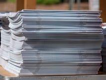 Pila de periódicos sujetados con grapa que se sientan en una pila imagen de archivo
