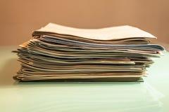 Pila de periódicos viejos en la tabla transparente - imagen imagen de archivo libre de regalías