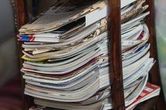 Pila de periódicos y de revistas en tabla de lectura Foto de archivo
